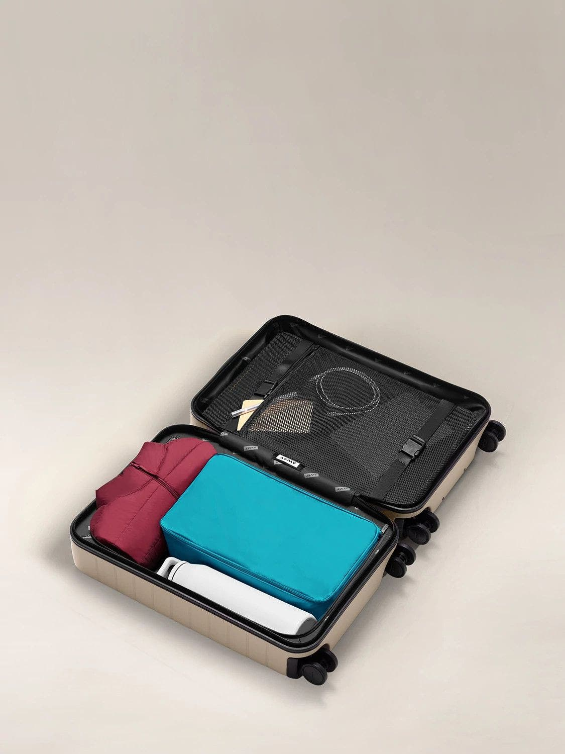 A large shoe cube in bright teal packed in an open carry-on suitcase.