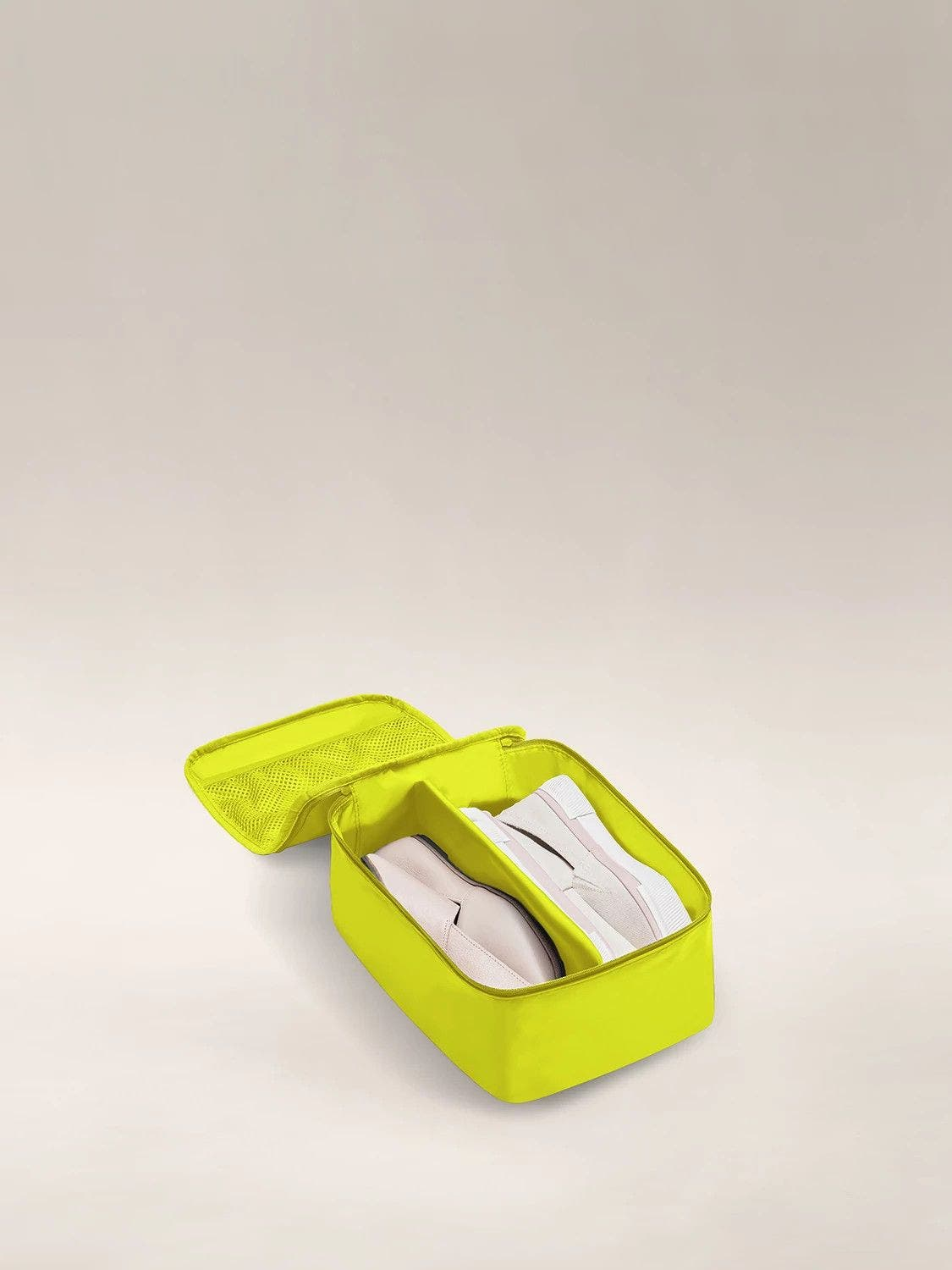 Open view of a small lime green shoe cube packed with a pair of sneakers.