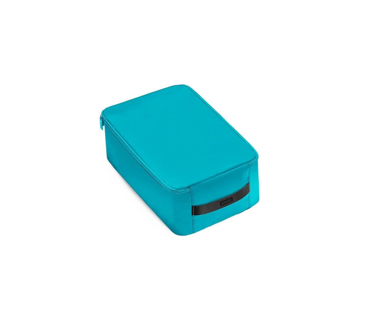A angled view of a small bright teal shoe cube.