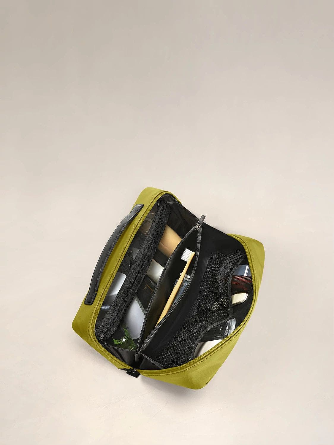Inside view of a travel toiletry kit in pistachio green with black interior pockets full of travel toiletries.