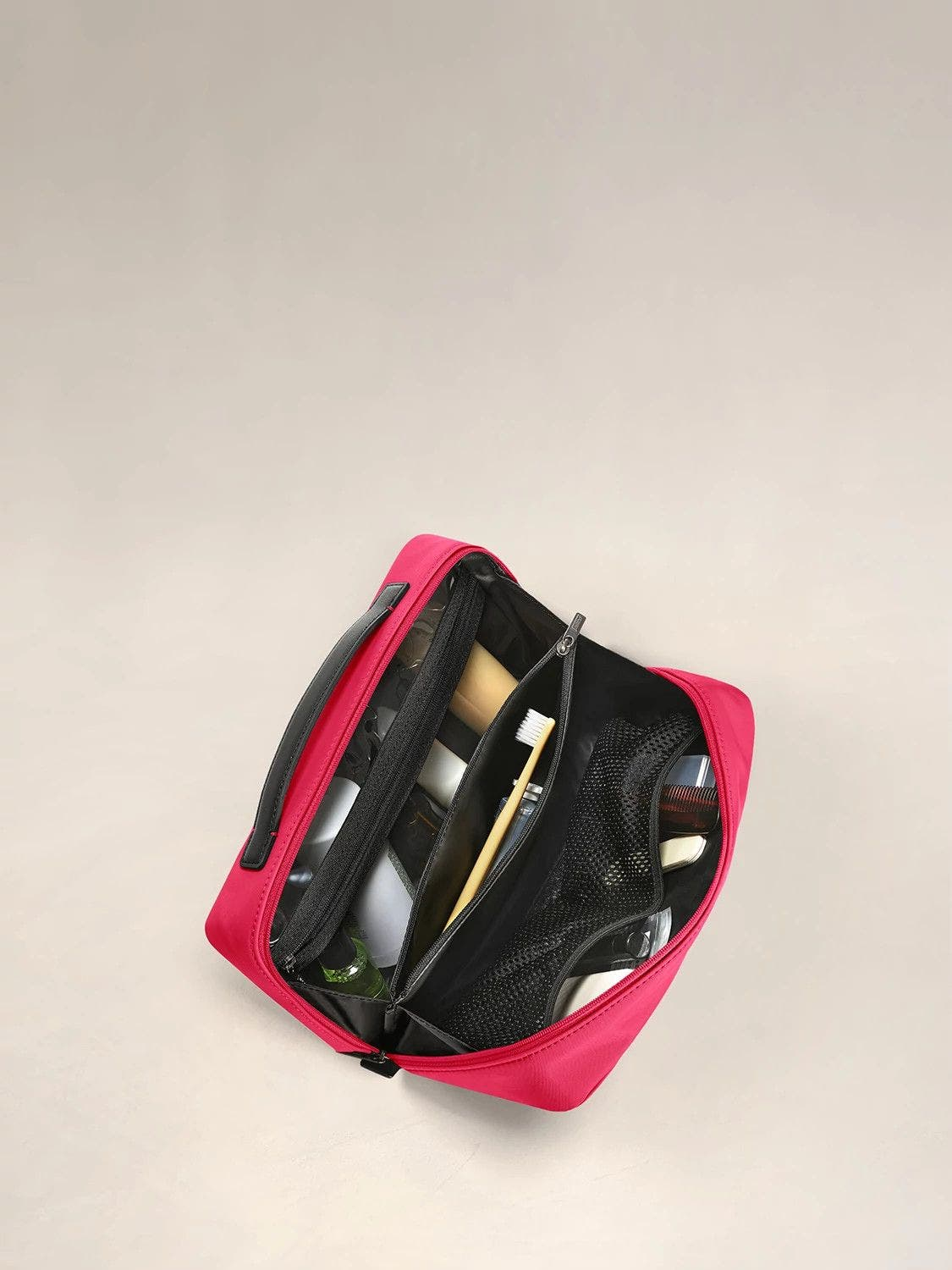 Inside view of a travel toiletry kit in electric magenta with black interior pockets full of travel toiletries.
