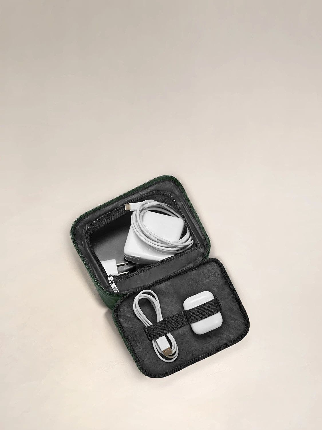 Inside view of a travel tech organizer with a white charger, ipod case and usb cord packed in its pockets.