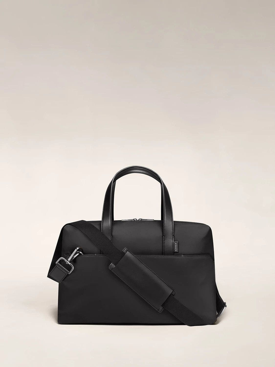 Black duffle with back zip pocket, and shoulder strap across the bag.