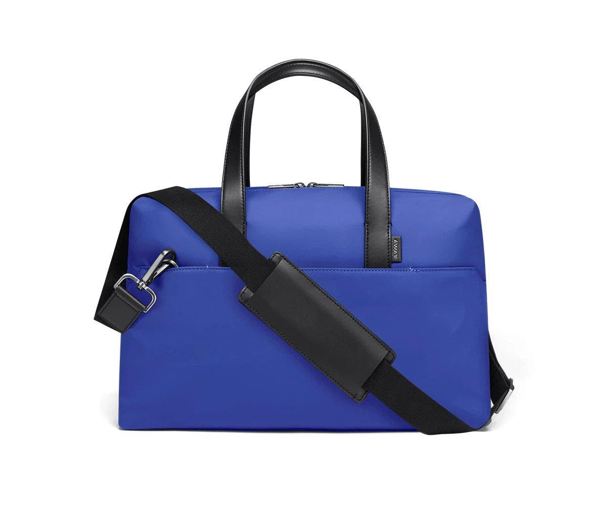 Cobalt duffle with back zip pocket, and shoulder strap across the bag.