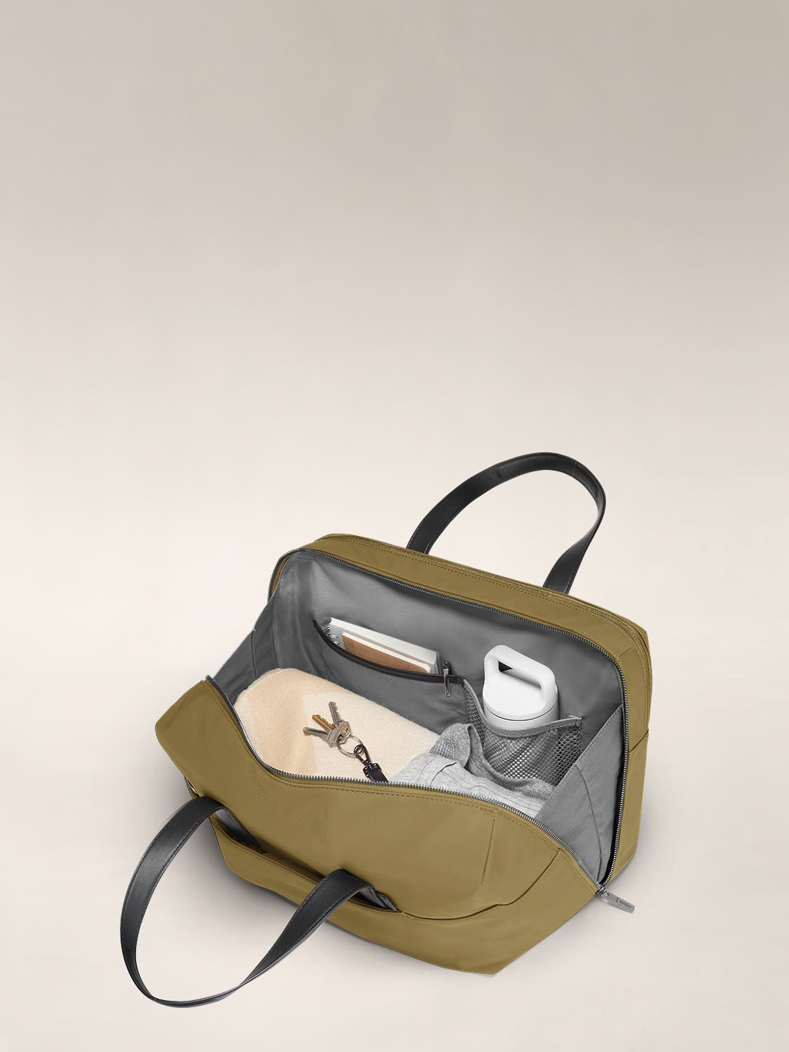 Open view of a Moss duffle bag with brown interior packed and organized with clothes, documents and water bottle in various internal pockets.