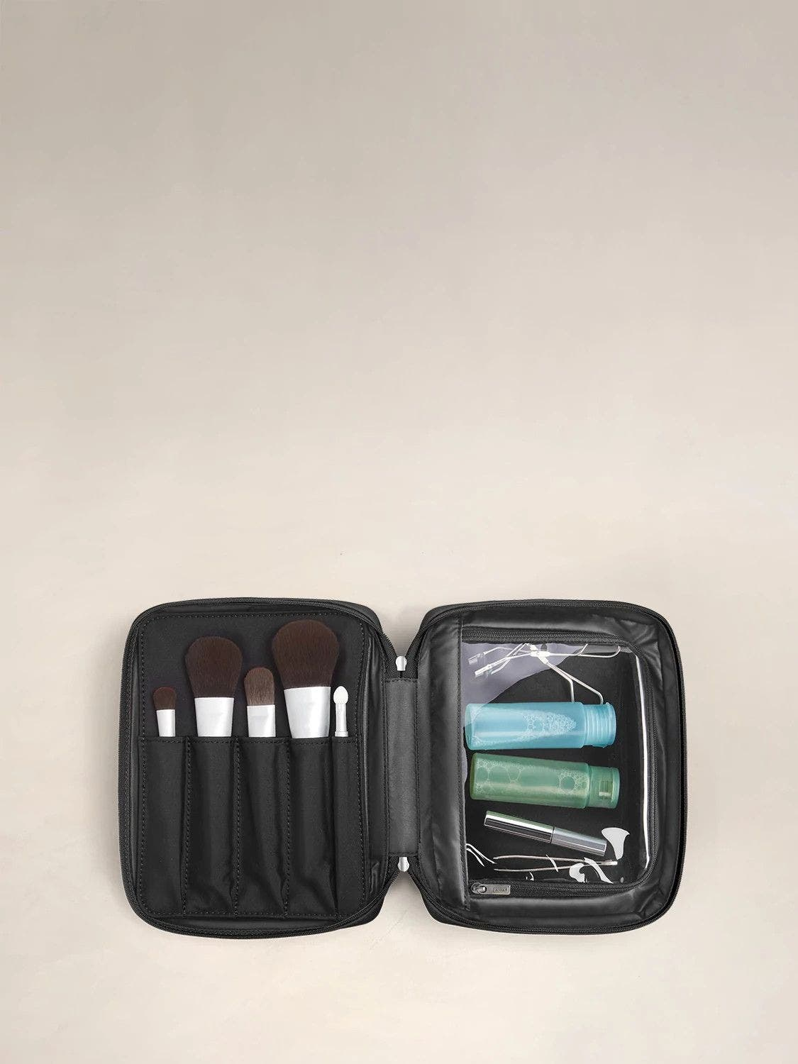 Open view of an Away black Cosmetics Bag in Nylon, with makeup brushes and travel sized toiletry items inside