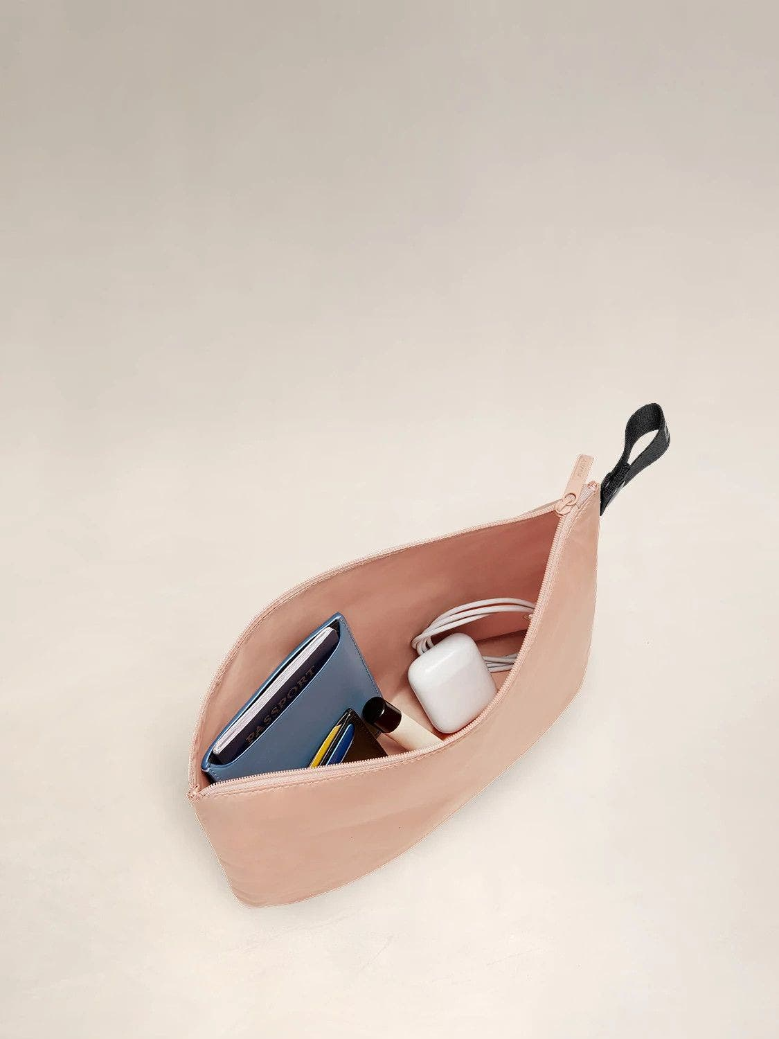 Open view of the Away large organizational travel pouch in the color petal pink filled with various packable items including airpods, chapstick and a phone charger