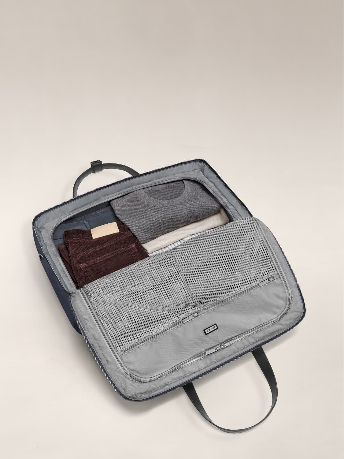 Open large shoulder bag with flap flat and gray interior packed with clothes.