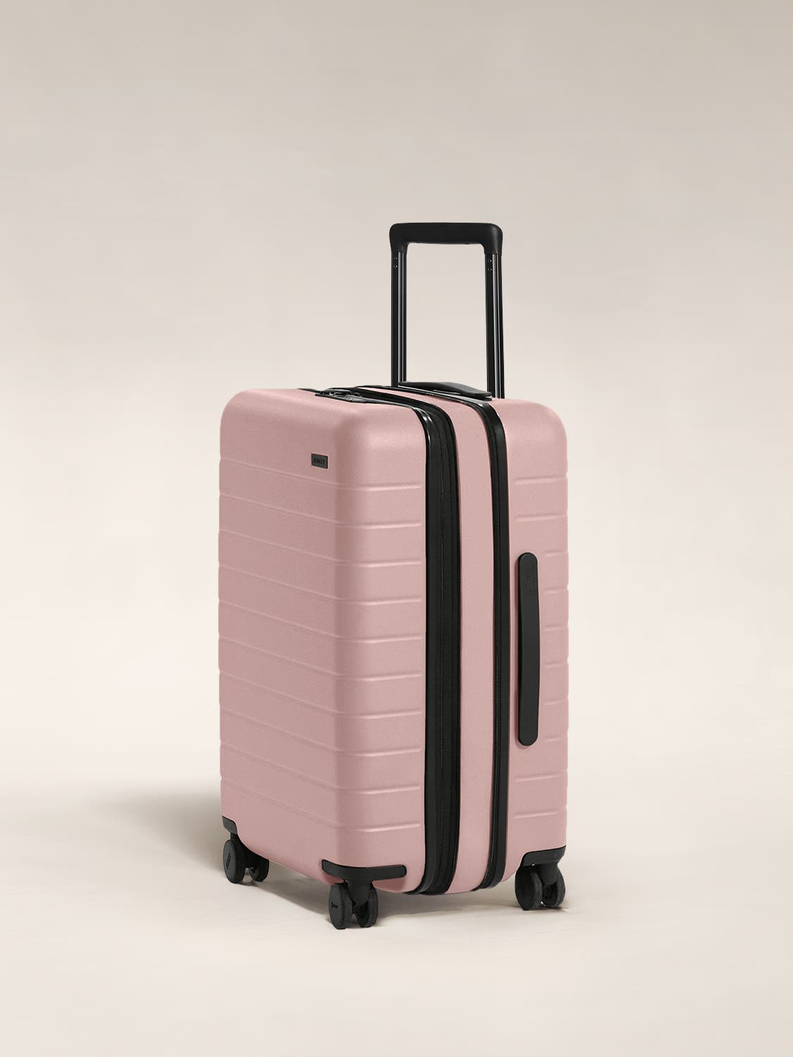 The Bigger Carry-On Flex in Petal shown at an angle with raised telescoping handle.