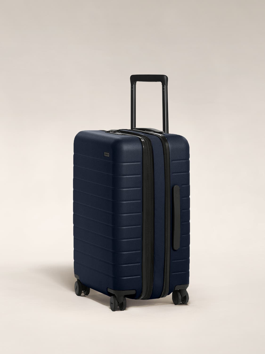The Bigger Carry-On Flex in Navy shown at an angle with raised telescoping handle.