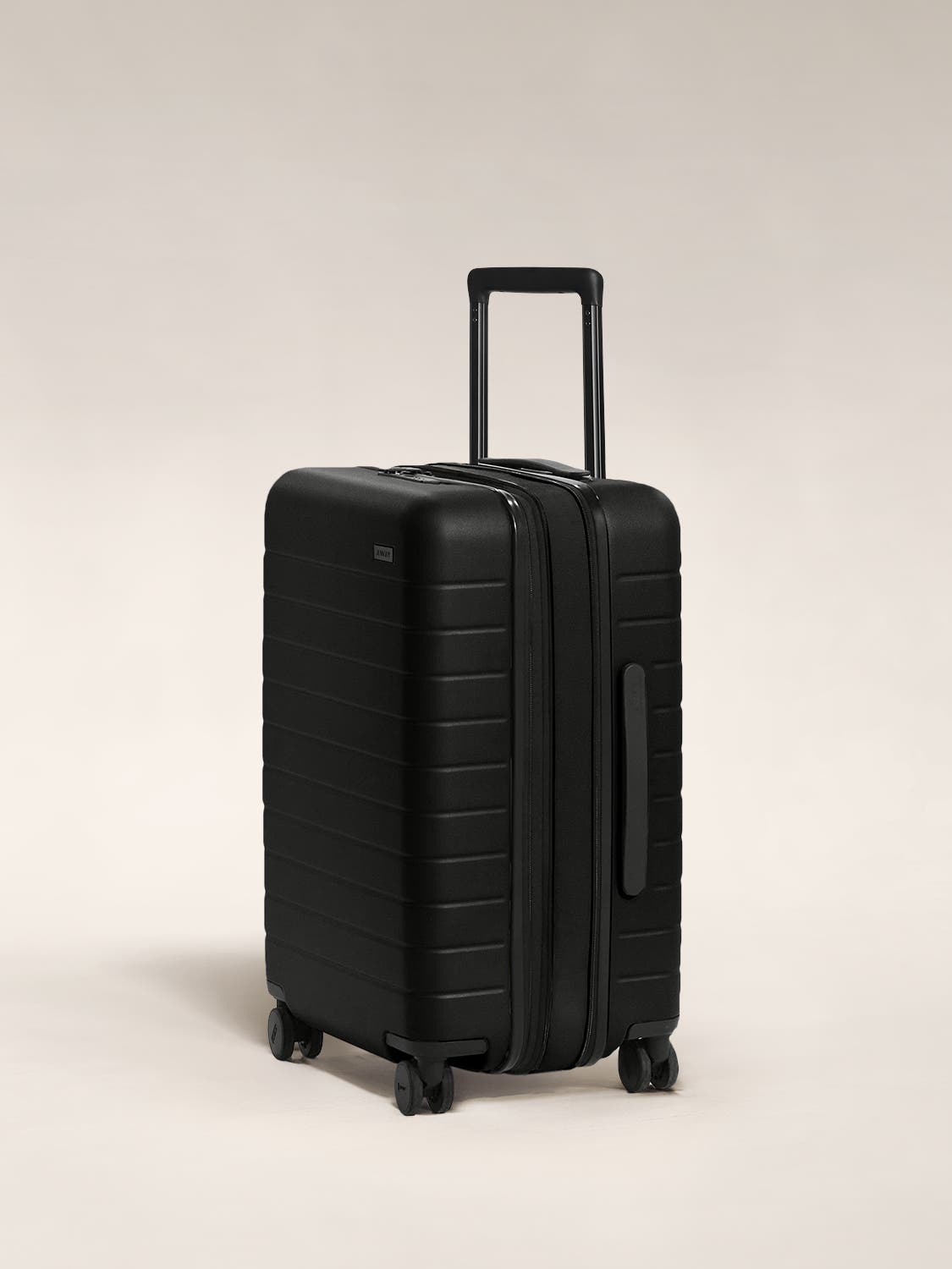The Bigger Carry-On Flex in Black shown at an angle with raised telescoping handle.