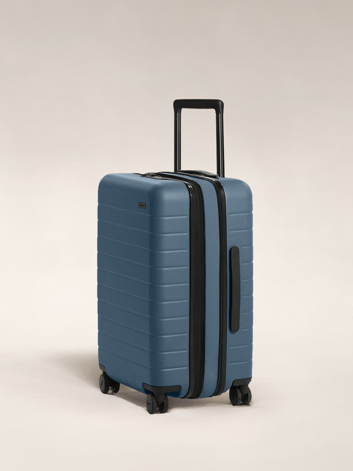 The Bigger Carry-On Flex in Coast shown at an angle with raised telescoping handle.