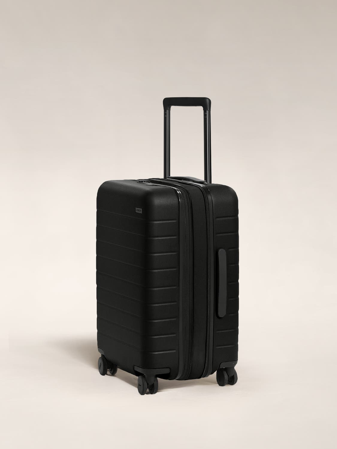 The Carry-On Flex in Black shown at an angle with raised telescoping handle.