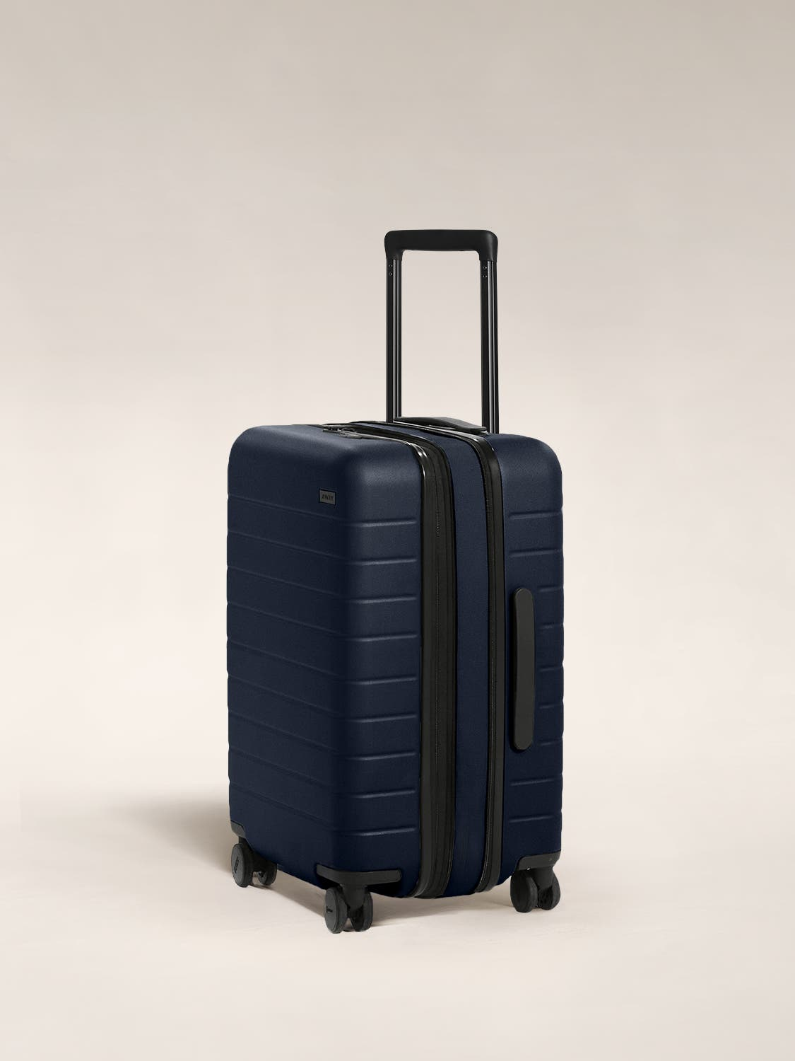 The Carry-On Flex in Navy shown at an angle with raised telescoping handle.