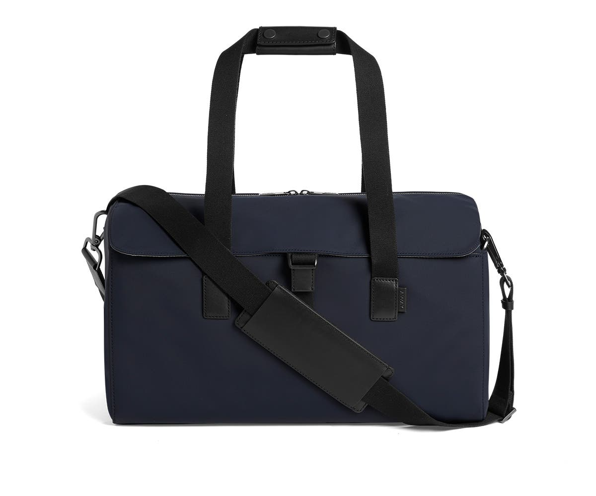 Flap black duffle bag in navy with raised handles and shoulder strap across the bag.