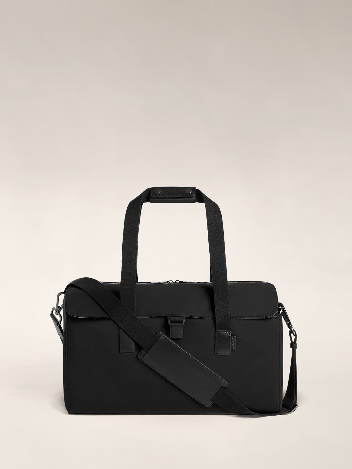 Flap black duffle bag in black with raised handles and shoulder strap across the bag.