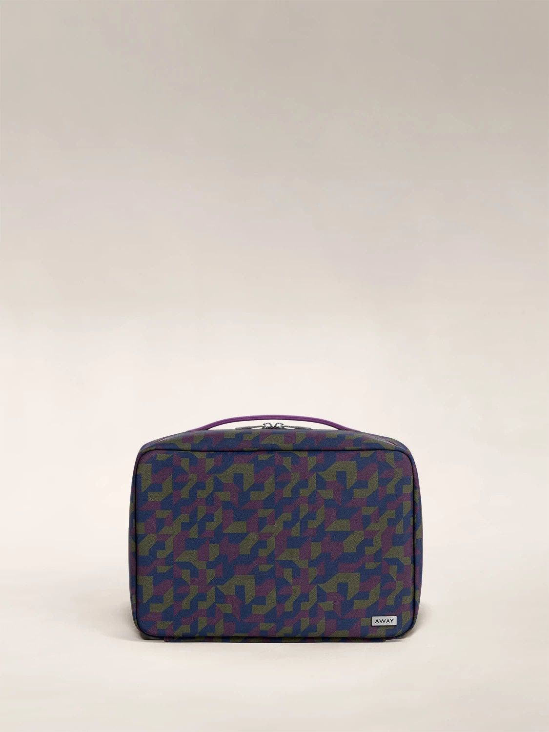 Front view of a geometric print toiletry bag with handle on top.