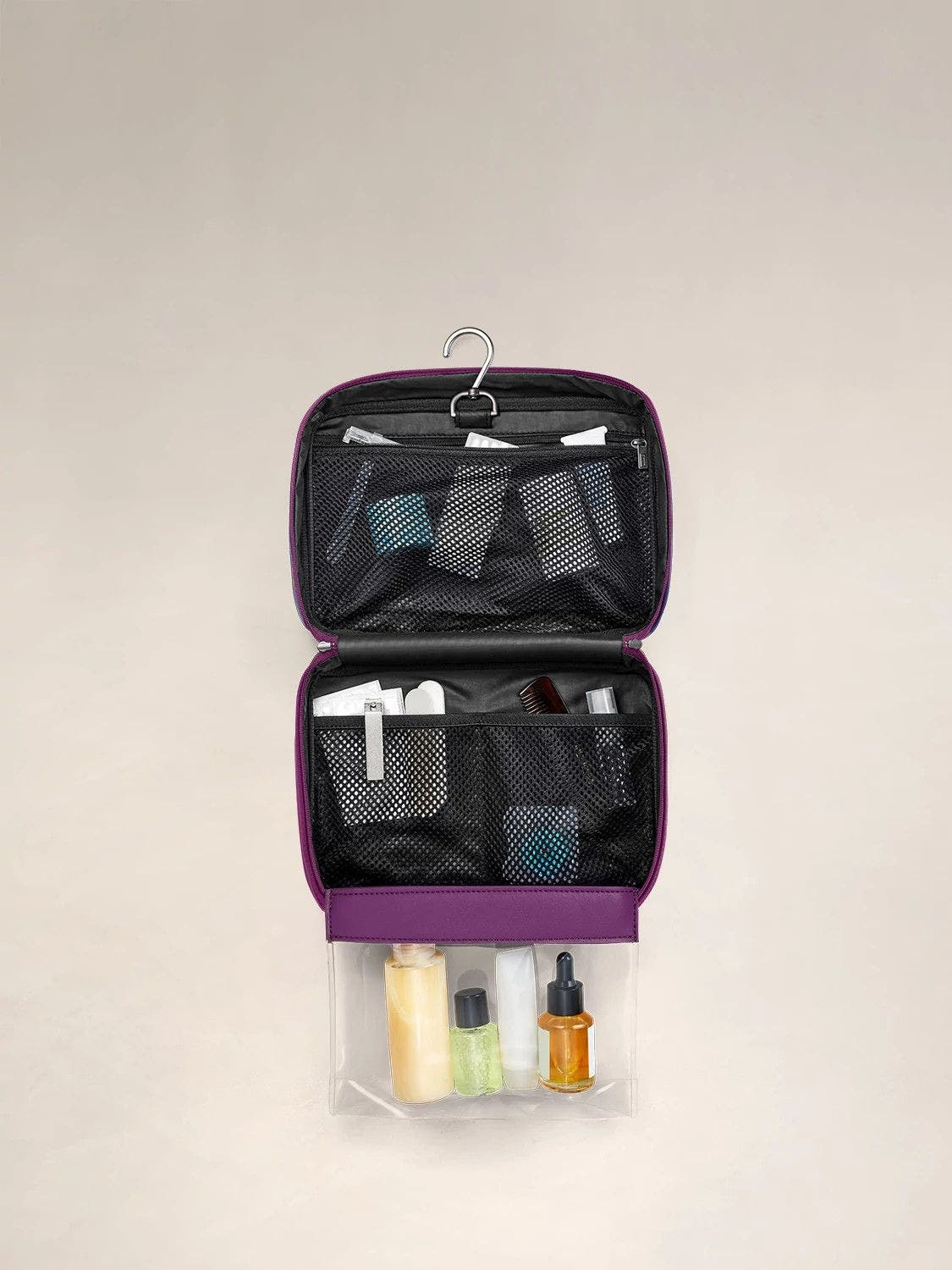 An internal view of a geometric print toiletry bag packed with travel accessories within mesh pockets.