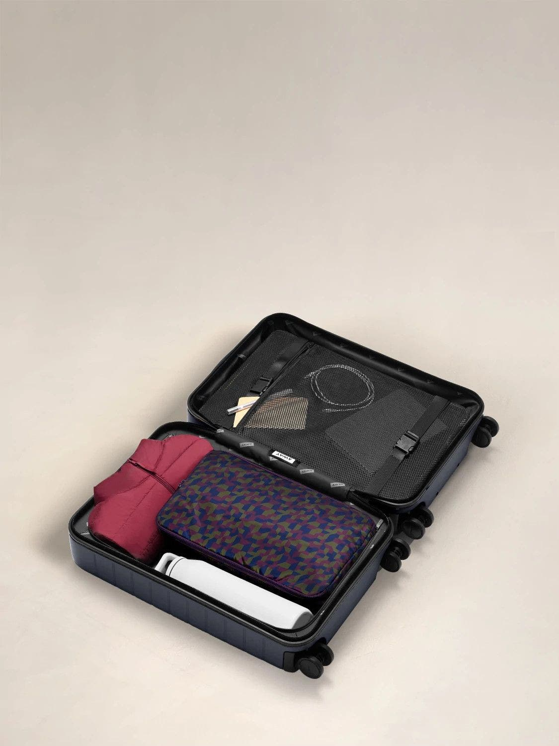 A large shoe cube in geometric print packed in an open carry-on suitcase.
