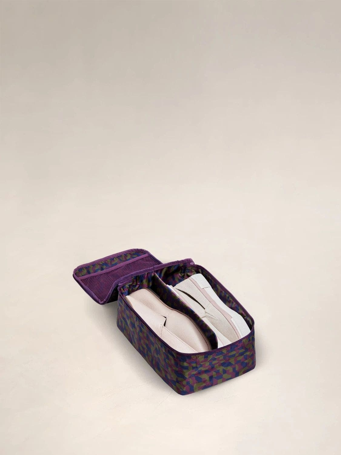 Open view of a small geometric print shoe cube packed with two pairs of shoes.