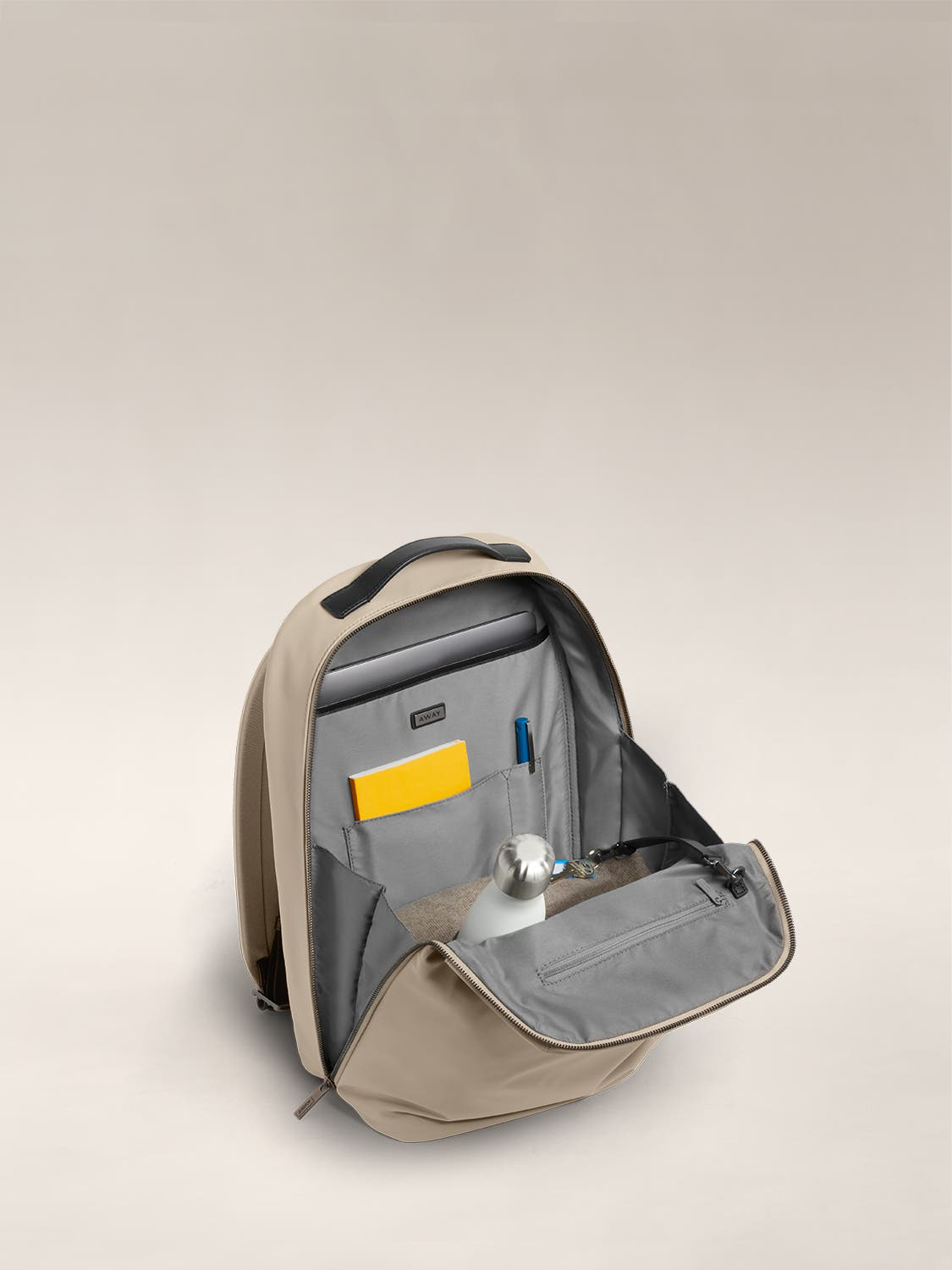 Open view  of a sand flap backpack with organized pockets shown with a yellow notebook, white water bottle, and a set of keys.