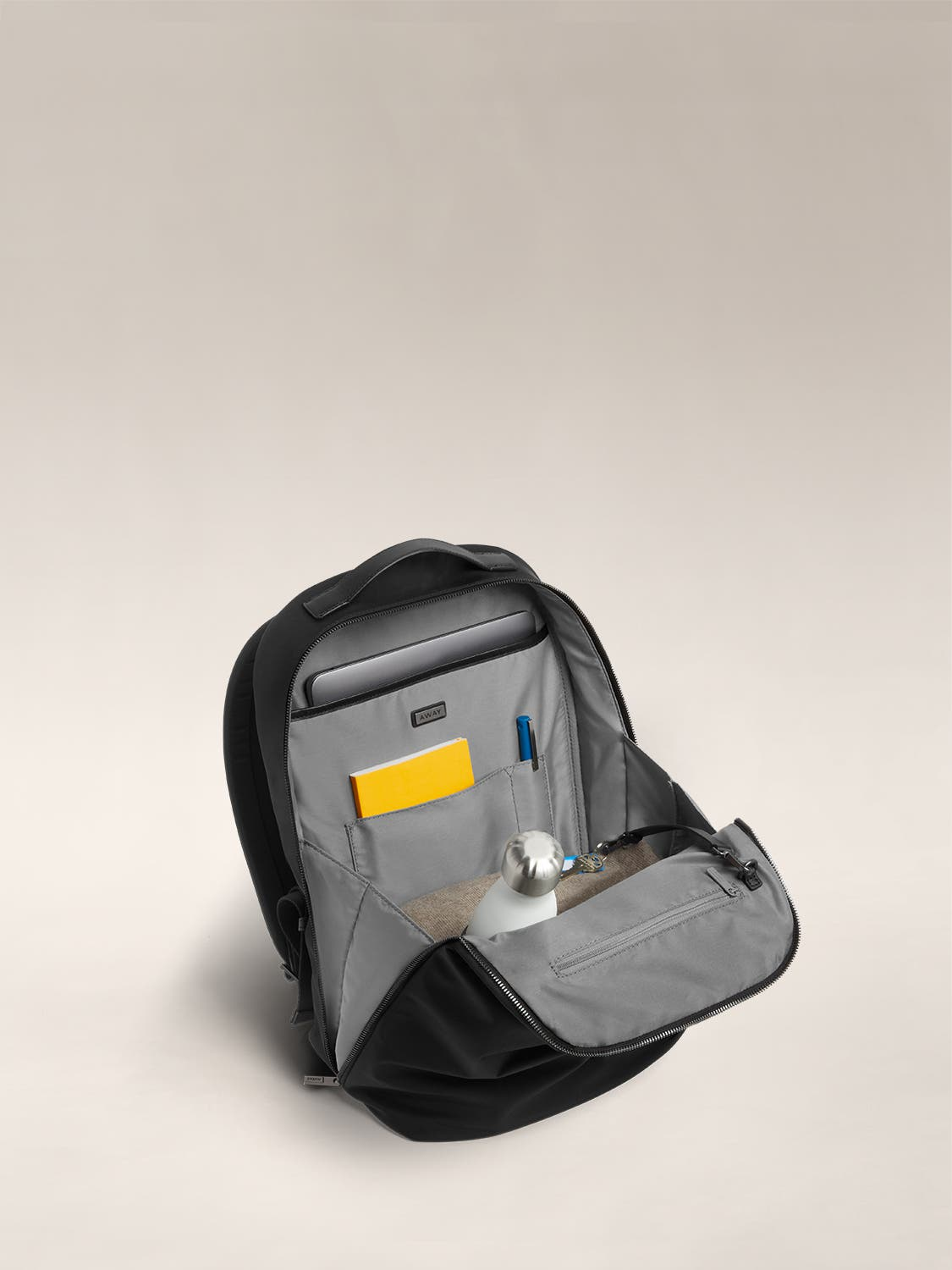 Open view  of a black flap backpack with organized pockets shown with a yellow notebook, white water bottle, and a set of keys.