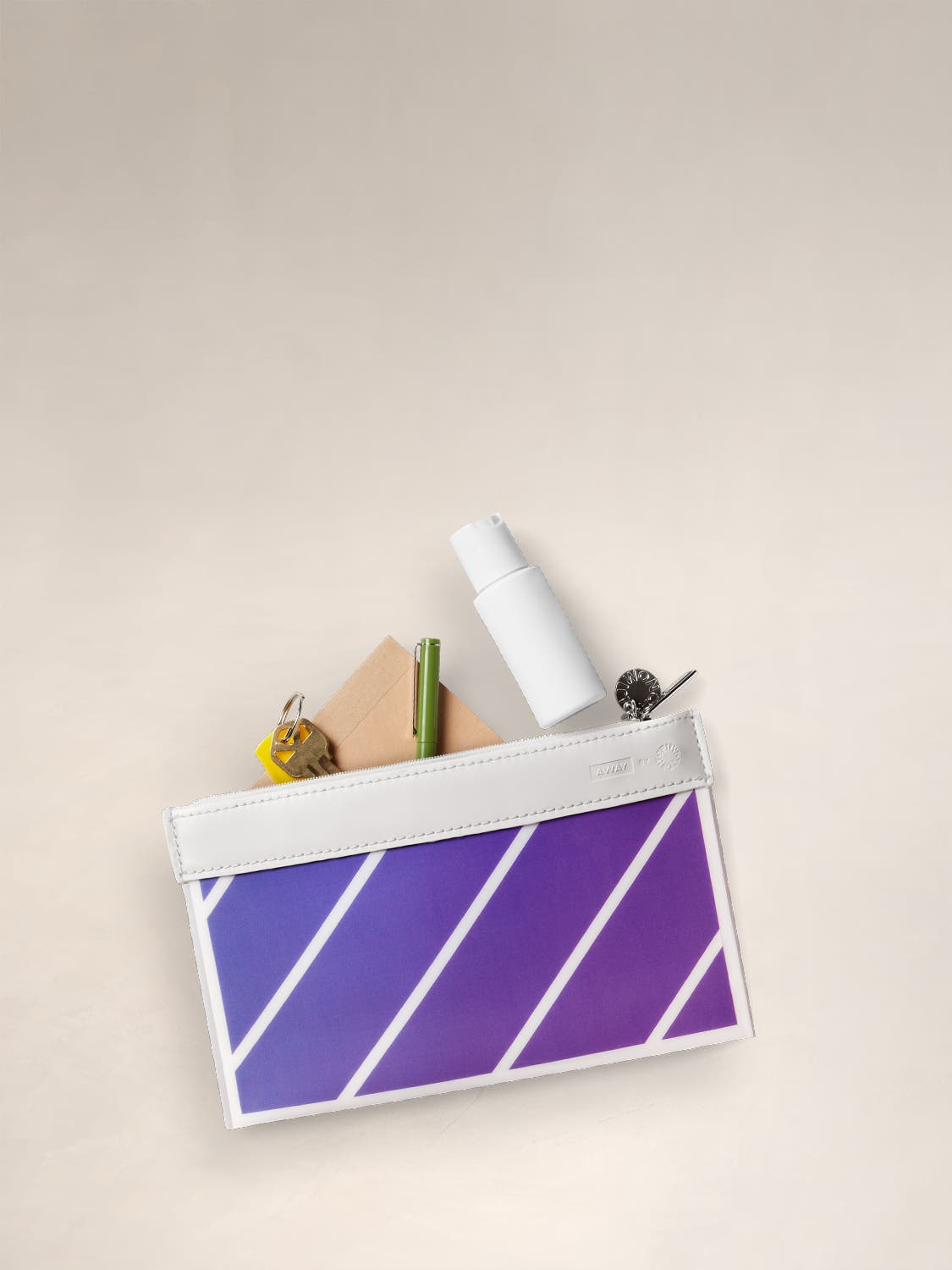 The Travel Pouch Set by Ji Won Choi in a purple stripe pattern, with miscellaneous items packed in