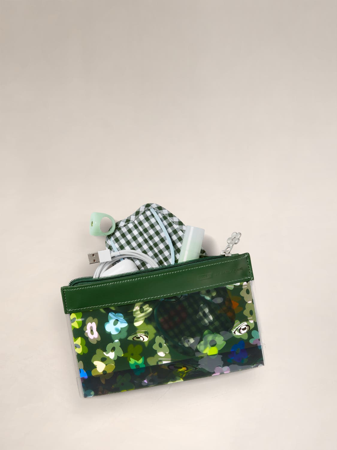 The Travel Pouch Set by Sandy Liang in green floral pattern, with miscellaneous items packed in