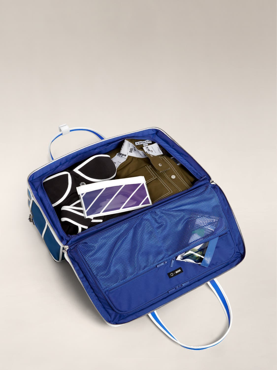 Open view of The Large Everywhere Bag by Ji Won Choi packed with clothes and a travel pouch