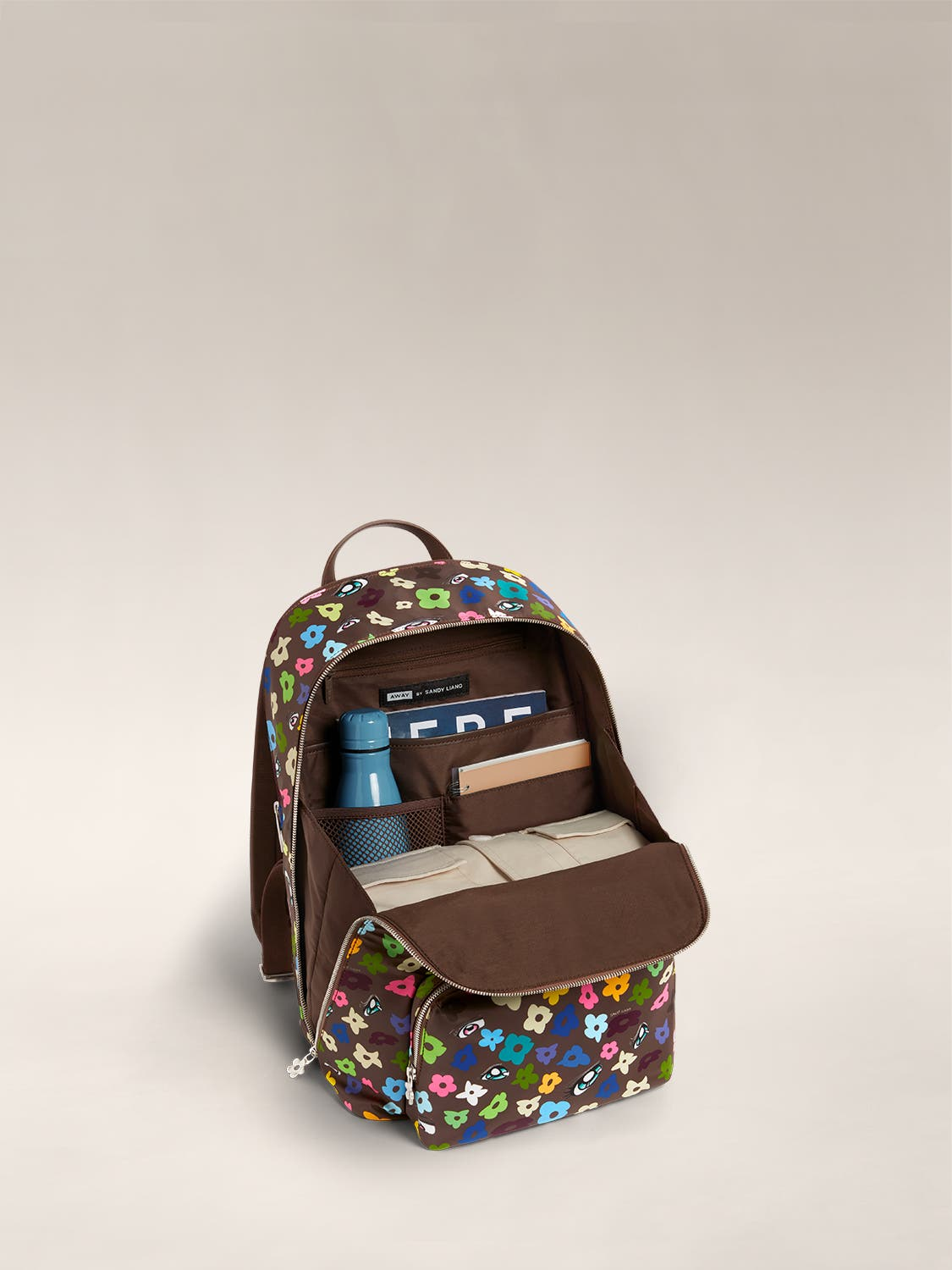The Front Pocket Backpack by Sandy Liang in brown floral pattern, open and packed with items such as a water hottle and wallet.