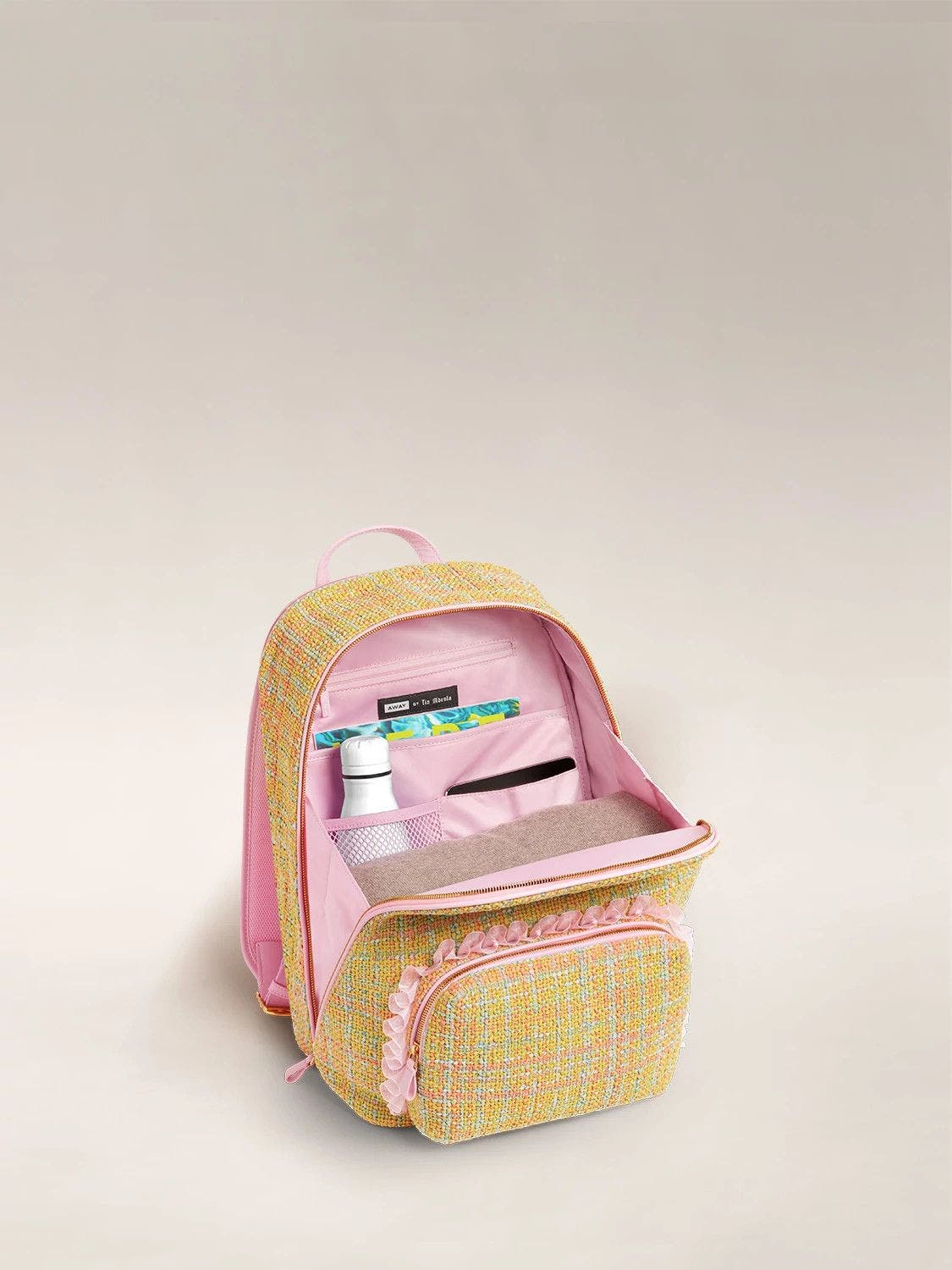 The Front Pocket Backpack by Tia Adeola in pink and yellow twill with pink ruffle details, open and packed with items such as a water hottle and wallet.