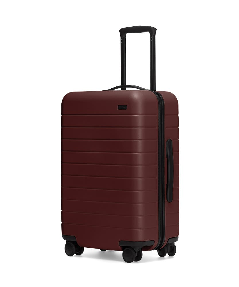 The Bigger Carry-On in Brick shown at an angle with raised telescoping handle