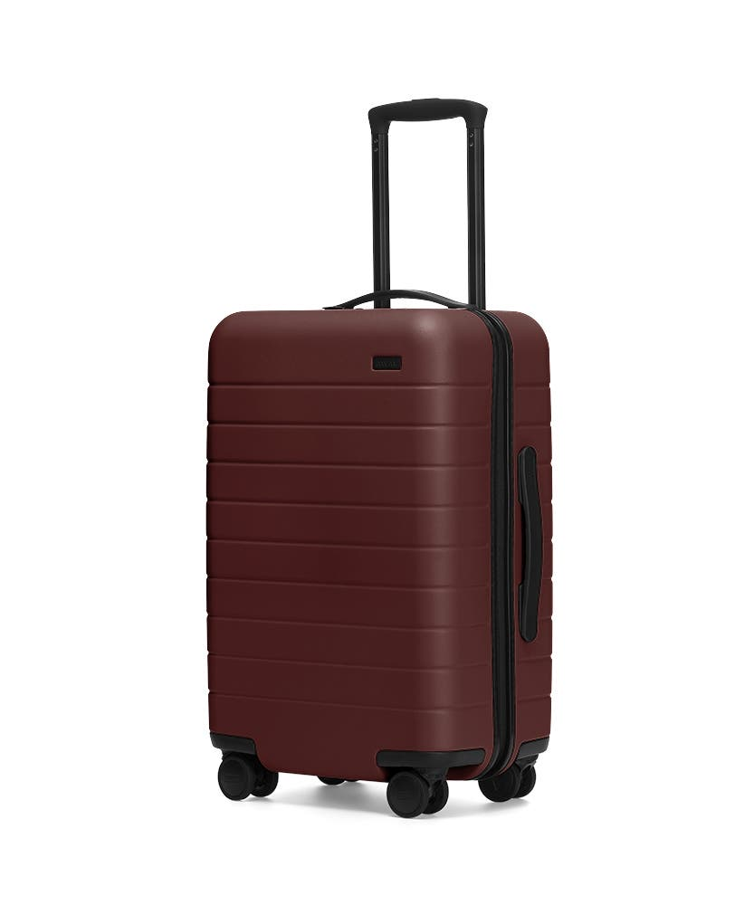 The Carry-On in Brick shown at an angle with raised telescoping handle