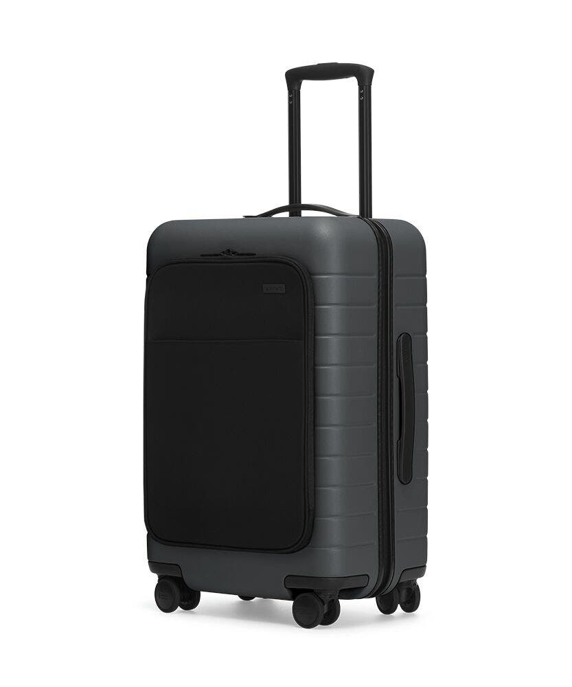 The Bigger Carry-On with Pocket in Asphalt shown at an angle with raised telescoping handle