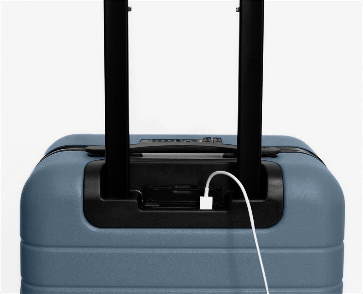 The Carry-On in Coast with charging cord plugged into battery underneath the telescoping handle